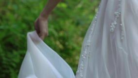 在瀑布附近的新娘盘旋的和挥动的礼服 股票录像