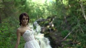 在瀑布附近的新娘盘旋的和挥动的礼服 股票视频