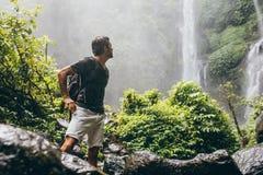 在瀑布附近的男性远足者在雨期间 库存图片