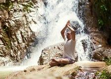 在瀑布附近的运动的年轻人实践的瑜伽在mountai 库存图片