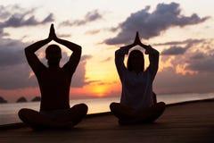 在瀑布附近的运动的年轻人实践的瑜伽在mountai 免版税图库摄影