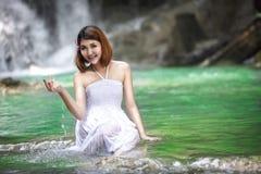 在瀑布附近的年轻亚裔妇女 图库摄影