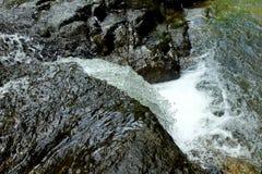 在瀑布顶视图的黑岩石 库存图片