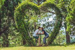 在灌木下的一对爱恋的夫妇以心脏的形式 St华伦泰` s天,爱概念 库存图片