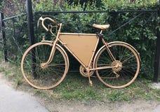 在灌木前面的金黄减速火箭的自行车 免版税图库摄影
