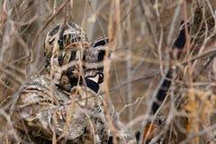 在灌木的暗藏的猎人 免版税图库摄影