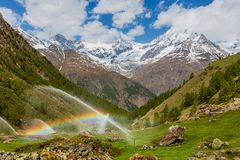 在灌溉水喷口的彩虹在阿尔卑斯山 免版税库存图片