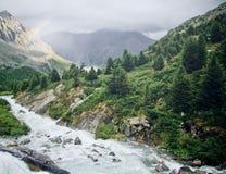 在灌溉水喷口的彩虹在山 库存图片