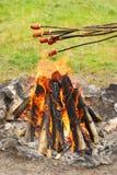 在火之上烤香肠棍子 免版税库存照片