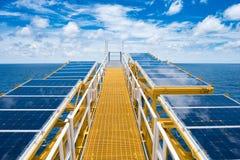 在火光桥梁的太阳能电池在电气系统充电的电池的油和煤气泉源遥远的平台在平台的 库存图片