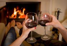在火前面的夫妇饮用的酒 免版税库存图片