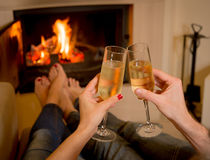 在火前面的夫妇饮用的香槟 免版税库存图片