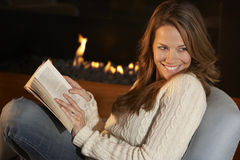在火前面的妇女读书在家 免版税库存照片