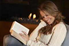 在火前面的妇女读书在家 库存照片