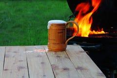 在火和草坪背景的一个杯子  库存照片
