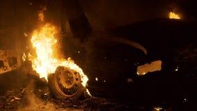 在火在晚上,燃烧的车轮,背面图的汽车 影视素材