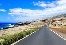 在火山倾斜和海洋之间的一条车道路 免版税库存图片