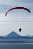在火山和海背景的滑翔伞飞行  库存图片