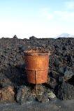 在火山的土地的生锈的垃圾桶 图库摄影