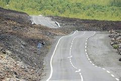 在火山的熔岩,雷乌尼翁冰岛,法国的弯曲的柏油路 库存照片