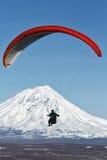 在火山背景的滑翔伞飞行  免版税库存照片
