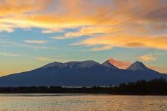 在火山Kluchevskaya小组的美好的日出与反射在河堪察加 库存图片