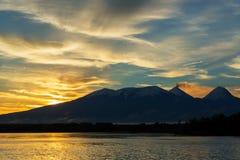 在火山Kluchevskaya小组的美好的日出与反射在河堪察加 免版税库存照片