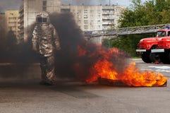 在火接近度衣服的Fiteman投入火 做保护他免受危险物料的火接近度衣服的消防员 免版税库存图片