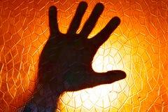 在火橙色颜色背景的手剪影 免版税库存照片