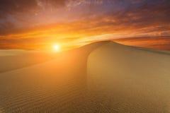 在火热的日落的背景的美好的沙漠风景 库存照片