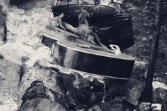在火焰和两口老煤烟灰大锅的吉他 图库摄影