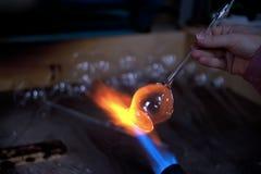 在火焰的熔化的玻璃片断 免版税图库摄影