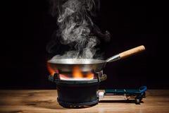 在火煤气喷燃器的中国铁锅平底锅 免版税库存照片