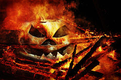 在火的一个蠕动的南瓜头 免版税库存照片
