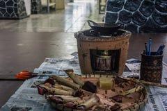 在火的倾斜的,热的蜡和为处理工具照片的蜡染布否决拍在北加浪岸印度尼西亚 免版税库存照片