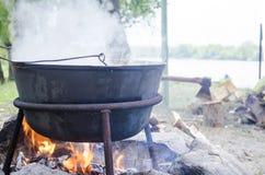 在火的大金属大锅 水为食物煮沸的旅游火 阵营罐,开水,旅游食物 锅炉工人 库存图片