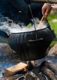 在火的大黑烹调罐户外 免版税库存照片