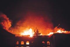 在火的屋顶大厦在晚上 库存照片