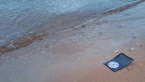 在火的数据CD的圆盘在海岸的沙子 股票录像