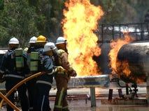 在火的汽油箱与紧急消防队员 库存图片