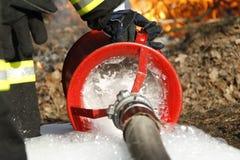 在火的灭火水龙带 免版税库存图片
