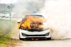 在火的灼烧的汽车在高速公路公路事故 免版税库存照片