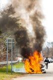 在火的灼烧的汽车在高速公路公路事故 库存图片