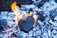 在火的烧心 木心脏被烧焦了和在煤炭的火焰 强的爱,灼烧的激情的概念,打破 库存图片