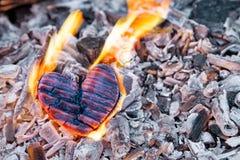 在火的烧心 木心脏被烧焦了和在煤炭的火焰 强的爱,灼烧的激情的概念 库存图片