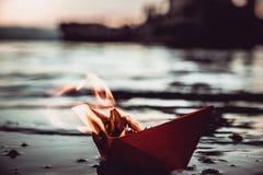 在火的红色纸小船 库存图片