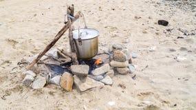 在火的罐在沙子 免版税库存图片