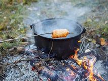 在火的香肠小圆面包 库存照片