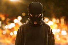 在火背景的恐怖分子佩带的面具 库存图片