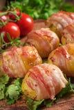 在火腿包裹的被烘烤的土豆 免版税库存图片